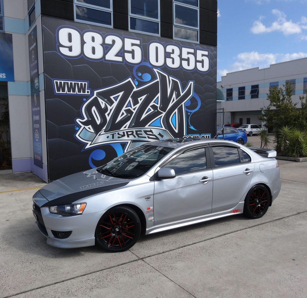 grey-jdm-mitsubishi-lancer-evo-fitted-with-black-and-red-hussla-rims